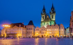 Tyn Cathedral and Old City Square in Prague illuminated at night.