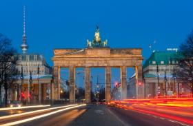 Brandenburger Tor mit Leuchtspuren und dem Fernsehturm Alex und Hotel Adlon